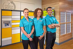 Associates at The UPS Store in front of 24 hour lockers